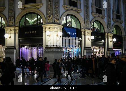 Milan, Italy - December 7, 2018: People shop for Christmas in front of the shop windows of PRADA luxury boutique store in Galleria Vittorio Emanuele - Stock Image