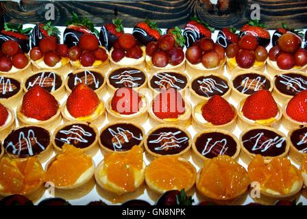 Assorted fruit & chocolate custard pastry tarts dessert buffet tray - Stock Image