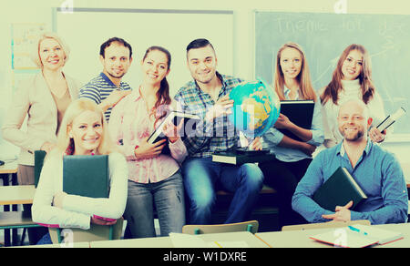 Portrait of friendly smiling teacher and happy students in classroom - Stock Image