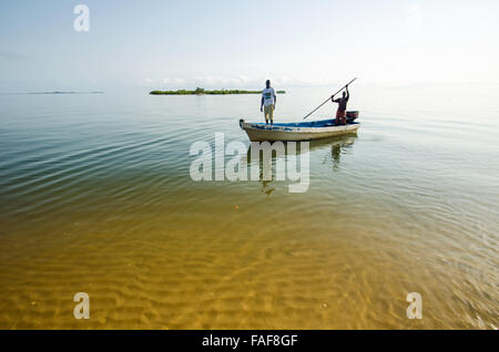 A small boat approaches Yele, in the Turtle Islands, Sierra Leone. - Stock Image