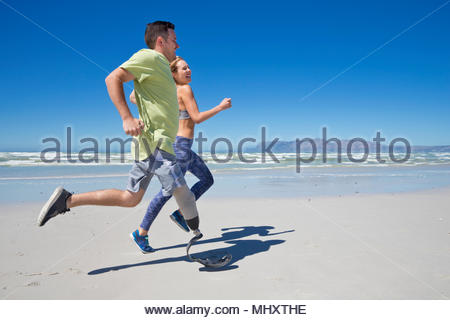 Side View Of Man Wearing Prosthetic Blade Running Along Shoreline Of Beach With Female Partner - Stock Image
