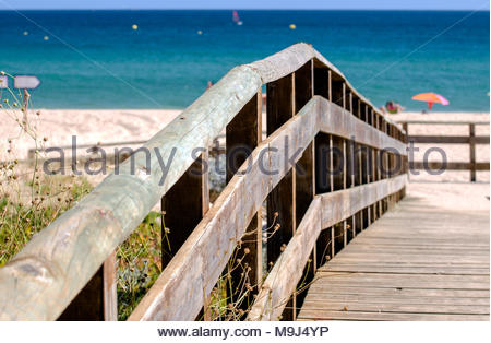 Hygge on the long golden sandy beach of Portimao, Portugal. Typical wooden footbridge on the Algarve. - Stock Image