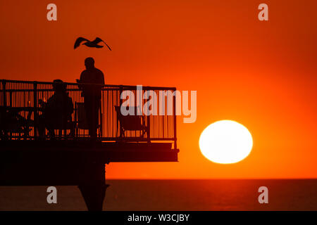 Aberystwyth Wales UK, Sunday 14 July 2019  UK Weather: People  - and a passing seagull - silhouetted against the orange colour of the sunset as they stand on  the seaside pier  in Aberystwyth at the end of a warm summers day  in west Wales.   photo credit: Keith Morris/Alamy Live News - Stock Image