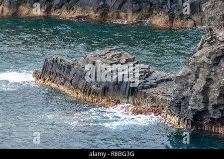 Volcanic basalt columns into the Atlantic Ocean on the coastline of La Palma Island - Stock Image