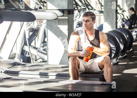 Portrait of athlete handsome masculine man sitting during treadmill exercise in gym, tired sportsman drinking water in sports hall. indoor, looking aw - Stock Image