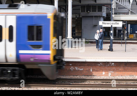 A motion blurred train passes Newcastle Central Station name board, Newcastle upon Tyne, England, UK - Stock Image