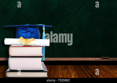 Education concept with blue graduation hat and diploma on stack of books on blackboard background. Copy space on chalk board. - Stock Image
