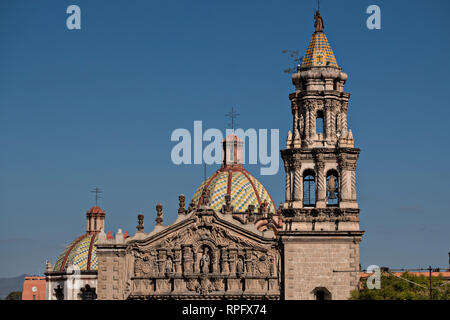 The tiled bell tower and domes on the Baroque Churrigueresque style Iglesia del Carmen church and convent in the historic center on the Plaza del Carmen in the state capital of San Luis Potosi, Mexico. - Stock Image