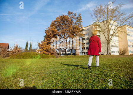 Old woman walking on meadow near houses - Stock Image