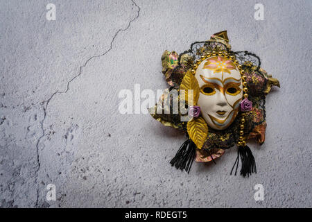 Decorative harlequin mask against a white wall background - Stock Image