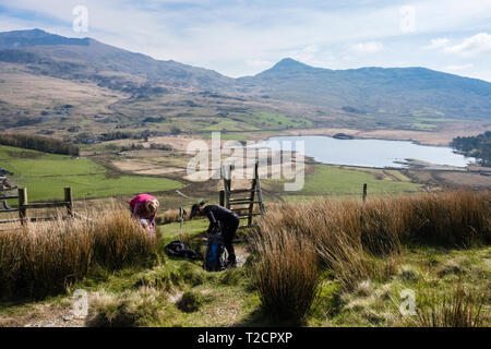 Two female hikers stopping to take off layers getting too warm on a hike up Y Garn on the Nantlle Ridge above Rhyd Ddu, Gwynedd, Wales, UK, Britain - Stock Image