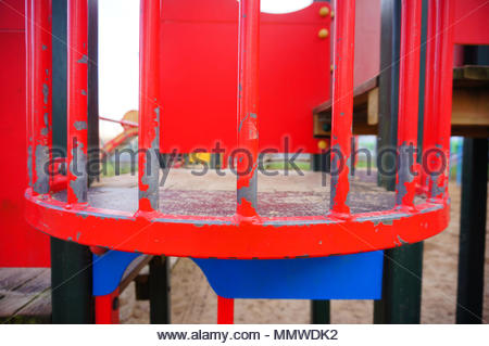 Close up of a red metal curve shaped barrier on a playground equipment - Stock Image