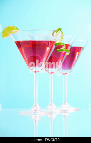 Stock image of three Cosmopolitan cocktails over blue background with reflection on bottom. Selective focus on front - Stock Image