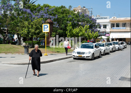 Old Greek lady crossing road by taxi rank, Rethymno, Crete Greece - Stock Image