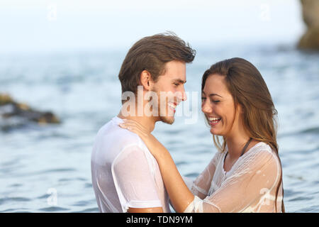 Happy couple laughing bathing on the beach on summer vacation - Stock Image