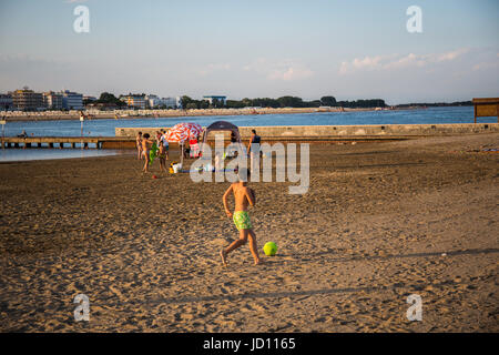 Caorle, Italy. 17 th June 2017. A kid having fun playing football on the beach at the evening. Credit: Lukasz Obermann/Alamy - Stock Image