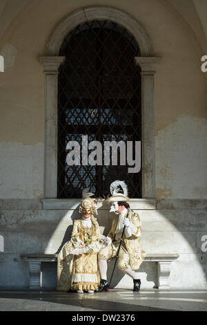 Venice, Italy. 25th Feb, 2014. A couple pose seated outside the Doge's palace in a shaft of light during Venice Carnivale Credit:  MeonStock/Alamy Live News - Stock Image