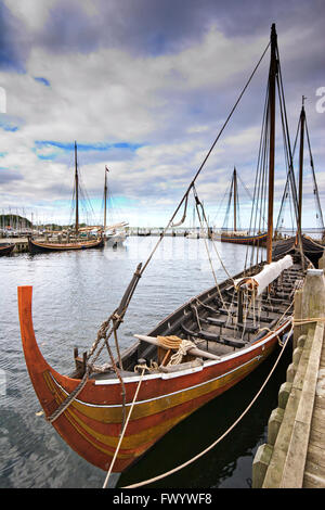 Replicas of Viking longships moored at the jetty of the Viking Ship Museum in Roskilde in Denmark. - Stock Image