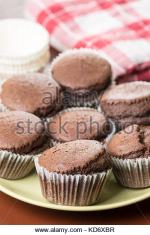 Fresh baked chocolate cup cakes served on the plate with kitchen dishtowel in the background. - Stock Image