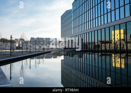 Piazza Antonio Olivetti, in the new Symbiosis district, Milan, Italy. The golden Haunted House of the Fondazione Prada is reflected in the building - Stock Image
