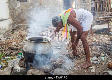 A man heating up water over an open fire for a morning bath in south India. - Stock Image