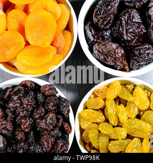 Selection of Healthy Dried Fruits Soft Apricots, Prunes, Raisins and Sultanas in White Bowls Looking Down With No People - Stock Image