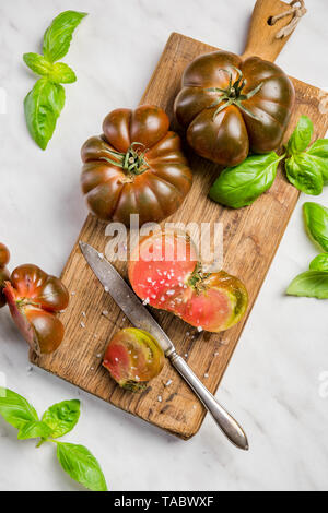 Chocolate tomatoes with basil on cuttin board. - Stock Image