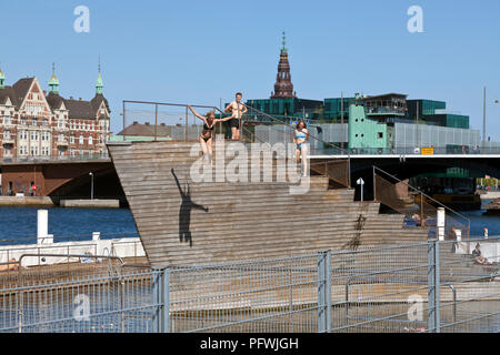 Girl jumping from the diving tower of Islands Brygge Harbour Bath in the inner harbour in central Copenhagen, Denmark on a sunny and warm summer's day - Stock Image
