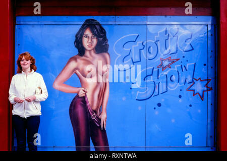 young female tourist standing by the entrance to a live sex show on the reeperbahn hamburg 1980s - Stock Image