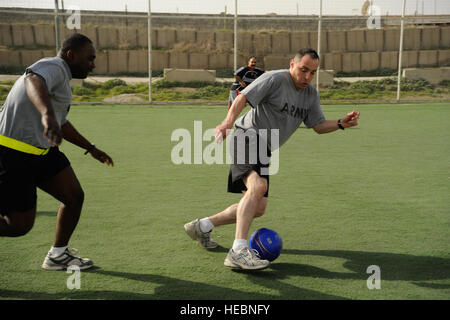 U.S. Army Sgt. 1st Class Diego Sanchez (right) kicks the ball away from Sgt. 1st Class Robert Edwards, 1st Battalion, - Stock Image