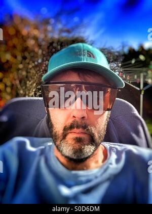 Middle aged man wearing blue hat, t-shirt and sunglasses, with blurred background and feeling of isolation - Stock Image