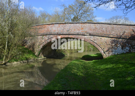 The Oxford Canal meanders through the Warwickshire countryside near the village of Wormleighton. One of the many bridges over the canal which are indi - Stock Image