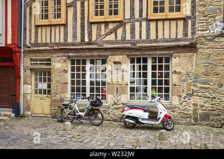 An electric bike and motor scooter outside a shop in Rennes, the capital of Brittany, France - Stock Image