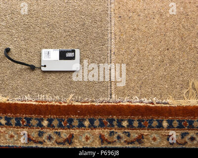 Colour matching carpet samples in an English home using a neutral grey card for colour fidelity - Stock Image