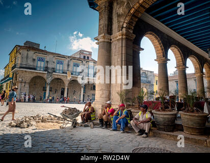 Workmen take a break from the midday sun and heat in Plaza Vieja, old Havana, capital of Cuba - Stock Image