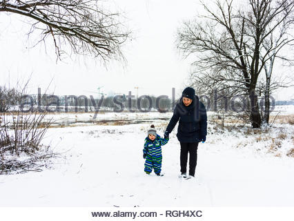 Poznan, Poland - January 26, 2019: Mother and son holding hands and walking on white snow at a park on a cold winter day. - Stock Image