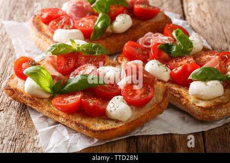 Ciabatta sandwiches with mozzarella, tomatoes, ham and basil close-up on the table. horizontal - Stock Image