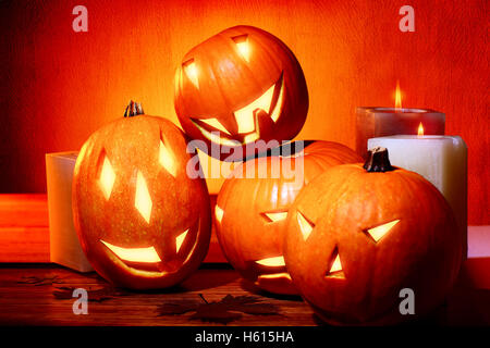 Stylish Halloween decorations, carved pumpkins with scary faces and candles as decor for Halloween party - Stock Image