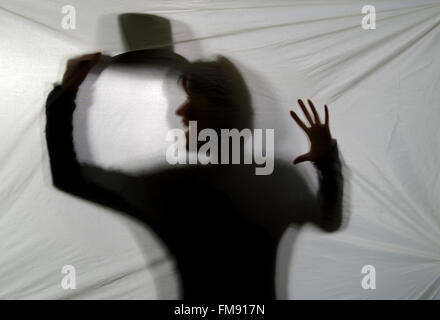 Dance of shadows. Young woman doing pantomime behind the canvas. - Stock Image