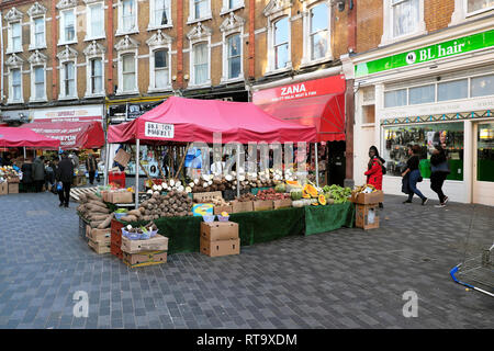 Vegetable stall & row traditional terraced housing above shops on Electric Avenue street market in Brixton South London SW9 England UK KATHY DEWITT - Stock Image