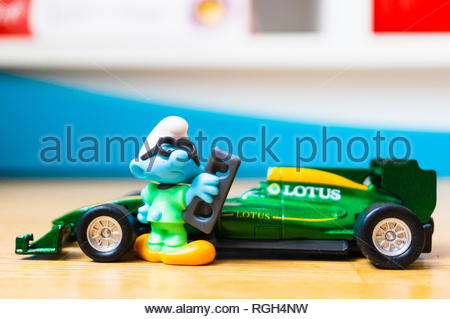 Poznan, Poland - January 20, 2019: Plastic toy Smurf with glasses standing next to his parked Formula 1 car. - Stock Image