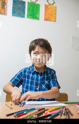 Boy enjoying with colored pencils while looking at camera, Munich, Germany - Stock Image