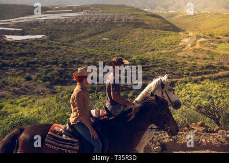 Young people in outdoor leisure activity together in couple enjoying a riding on her horse brown and white on a beautiful mountain valley - people wit - Stock Image