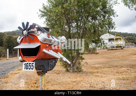 Roadside Mail Box Styled from an oil drum as an V8 Engine with Homestead in Background. Southern Queensland Australia. - Stock Image