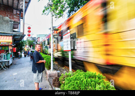 SHIFEN, TAIWAN - JUL 15, 2013: A villager waits for one of the many Pingxi trains to run through the heart of Shifen town center. Originally built for - Stock Image