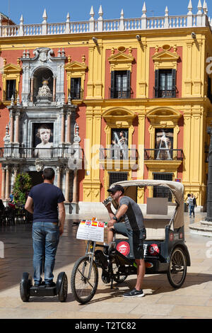 A segway rider and a bicycle taxi outside the Bishop's Palace, Plaza del Obispo, Malaga old town, Malaga, Andalusia Spain - Stock Image