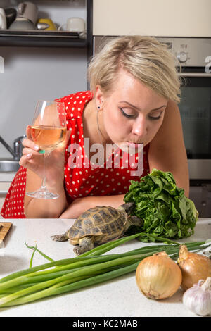 Female is surprised on tortoise who is eating salad - Stock Image