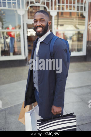 Portrait smiling, confident young man with shopping bags outside storefront - Stock Image
