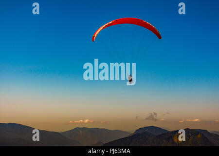 Paraglider silhouette flying over misty mountain valley in beautiful warm sunset colors - sport, active wallpapers full of freedom. Background with sp - Stock Image