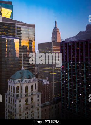 The early evening skyline of Midtown Manhattan in New York showing the Empire State Building as the sun is setting - Stock Image